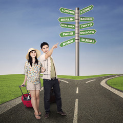 Asian couple travel with road signs outdoor