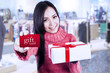 Attractive female shopper show gift card and box