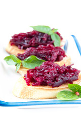 Classic Italian snack bruschetta with baked beet and fresh basil