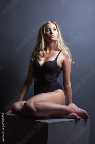 Slender young model posing sitting on cube