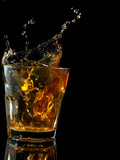 Glass of whiskey with splash, isolated on black