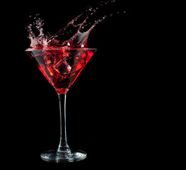 red cocktail splashing into glass on black