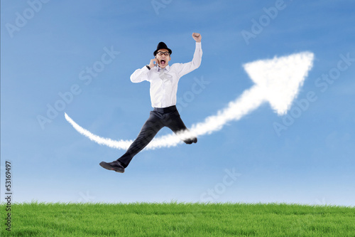 Businessman jump and calling over success sign outdoor