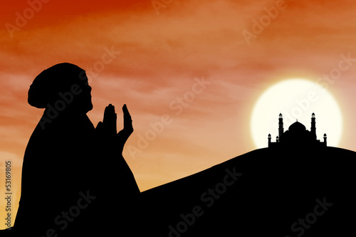 Background of female muslim silhouette  and mosque at sunset