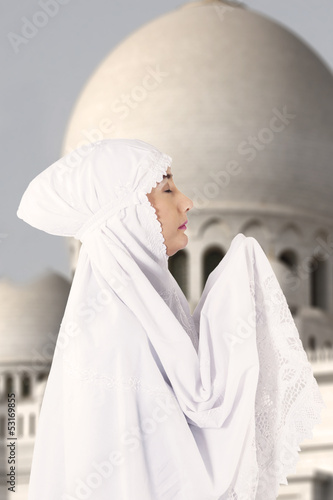 Female muslim in white praying at mosque