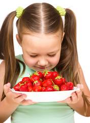 Happy little girl is eating strawberries