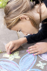 Girl drawing with chalk on pavement