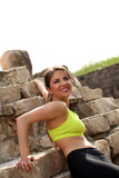 Beautiful woman in fitwear relaxing near stones