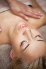 Beautiful young woman enjoys massage
