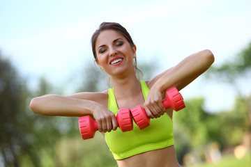 Beautiful woman working out with dumbbells