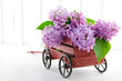 Decorative wooden carriage full of lilacs