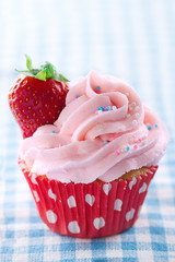 Pink cupcake with fresh strawberry and copy space