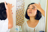 Asian woman discovering a pimple in face poster