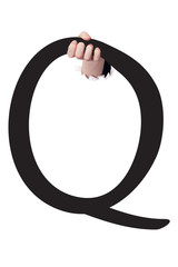 Hand breaking paper surface holding letter 'Q'