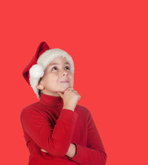 Pensive child with blond hair and Christmas hat
