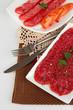 Tasty salami on plates on  napkin isolated on white