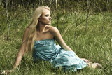 Beautiful blond woman sitting on green grass