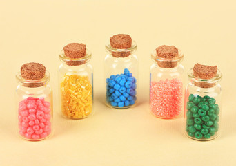 Different colorful beads in bottles on beige background