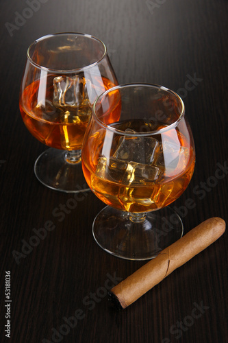 Brandy glasses with ice on wooden background
