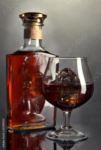 Brandy glass with ice and bottle on grey background