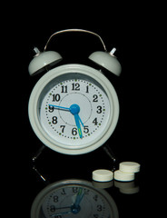 Old style alarm clock  and pills, isolated on black