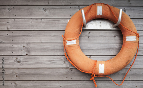 Red lifebuoy with rope on weathered wooden wall