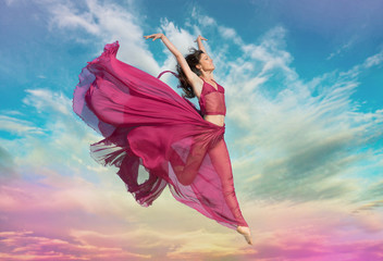 Woman in airy crimson dress jumping in the air at sunset