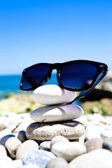 Occhiali da sole appoggiate sulle rocce con sfondo di mare