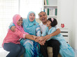 Excited Southeast Asian family at home. Muslim family living lif