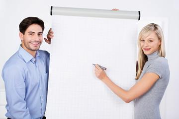 kollegen im büro stehen vor weißem flipchart