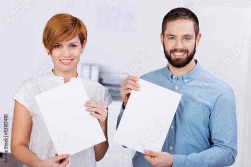 zwei auszubildende im büro zeigen weiße schilder
