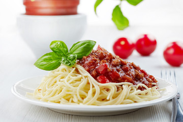 Spaghetti bolognese and green basil leaf on white plate