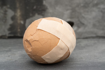 Broken healthcare concept image of plaster on egg