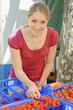 Freundliche Junge Frau kauft Erdbeeren auf Markt