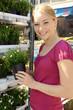Freundliche junge Frau kauft Blumen auf Markt