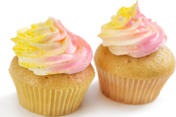 Two pink and yellow cupcake, isolated on white background