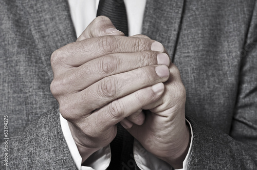 man in suit rubbing his hands