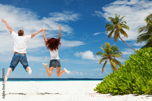 Happy couple jumping on the tropical beach