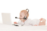Cute baby-operator with laptop on the white bed