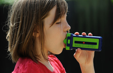 Young Asthma patient using a breath flow meter