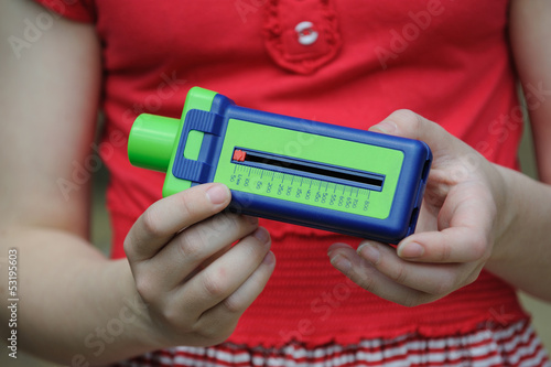 Young Asthma patient holding a breath flow meter