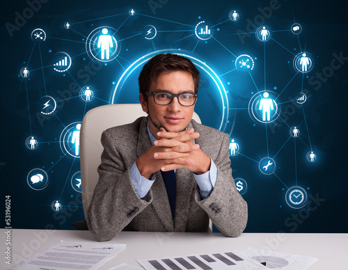 Businessman sitting at desk with social network icons