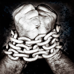 Hands locked by a strong chain on a black background