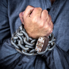 Hands of a formally dressed man chained with an iron chain