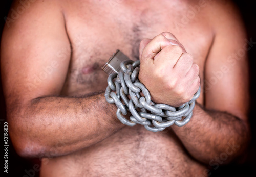 man with his hands chained with chains and a padlock