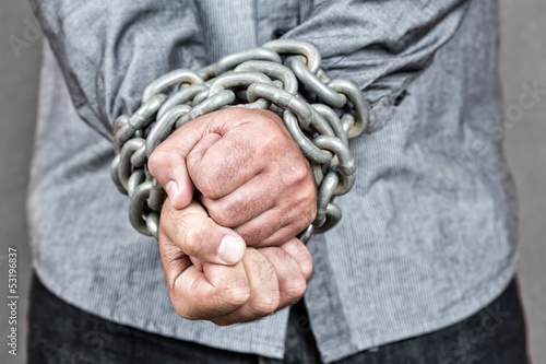 Close-up of a formally dressed man with his hands chained