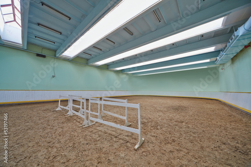 Indoor riding hall with sandy covering