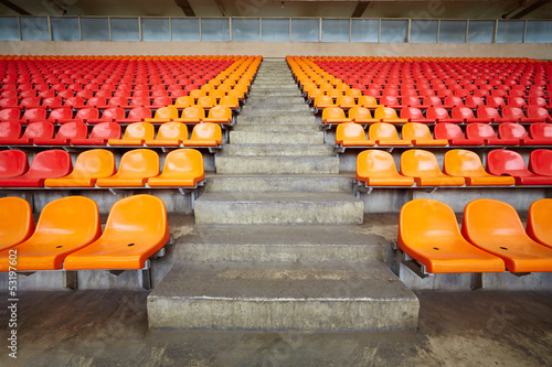 Rows of red and orange plastic sits at stadium
