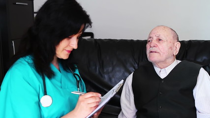 Nurse listening senior man and making notes