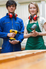 Two woodworking students standing before a workbench
